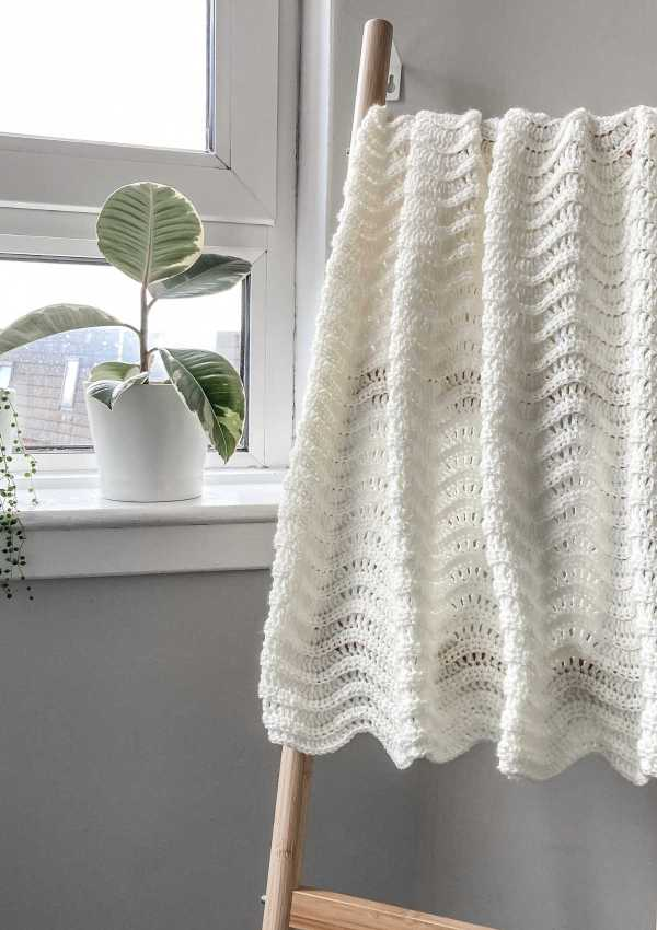 A small throw made with a gentle chevron crochet stitch shown hung over a blanket ladder, by a window with a plant on the sill