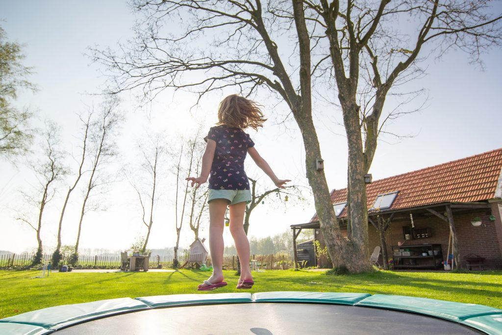 child exercising on a trampoline outside the house