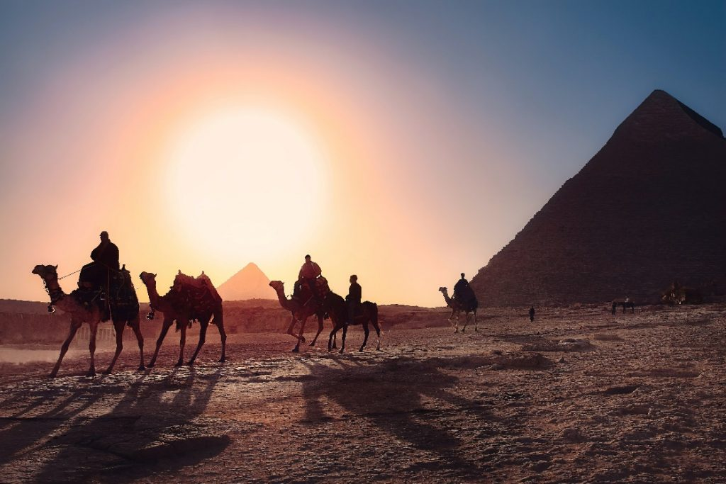 dragon-facts-–-sunset-at-Egypt-with-a-group-of-men-riding-camels-and-a-pyramid-on-the-side