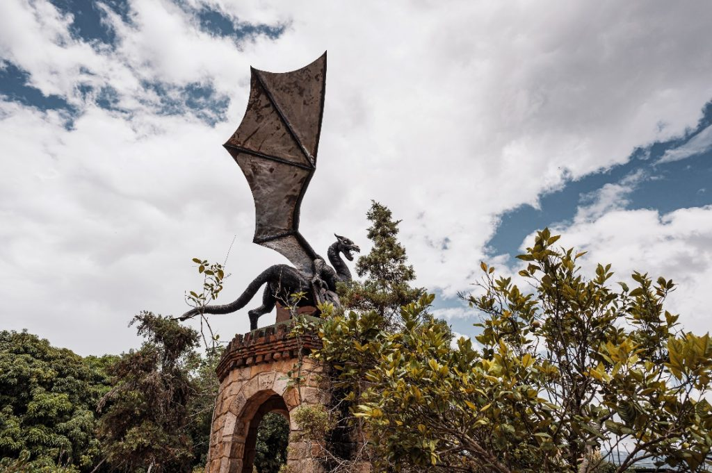 dragon-facts-a-black-gray-stone-dragon-on-top-of-a-brick-tower-with-trees-in-the-background
