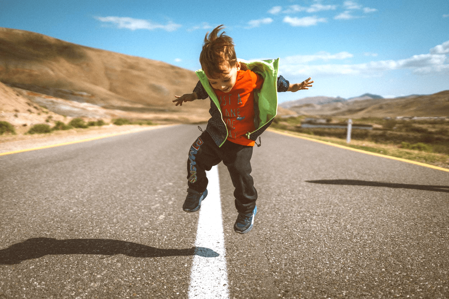 electric-rides-for-kids-a-young-boy-in-a-red-t-shirt-and-green-jacket-jumping-in-the-middle-of-the-road