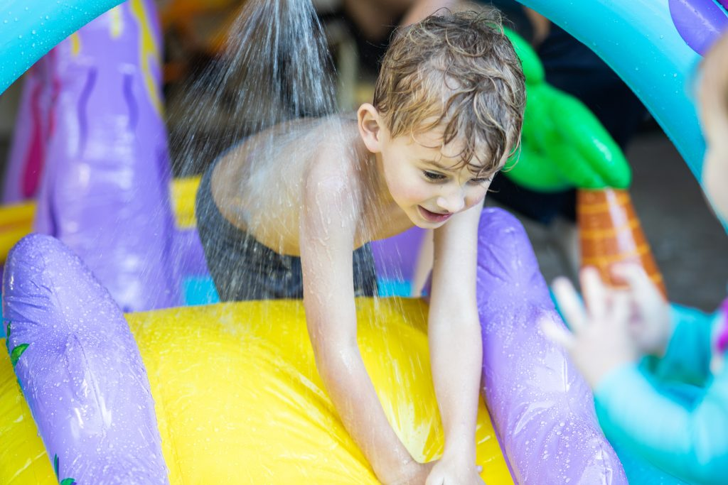 Top-8-Dinosaur-Water-Parks-You-Cant-Miss-This-Summer-2021-a-young-boy-playing-on-a-yellow-and-purple-slide