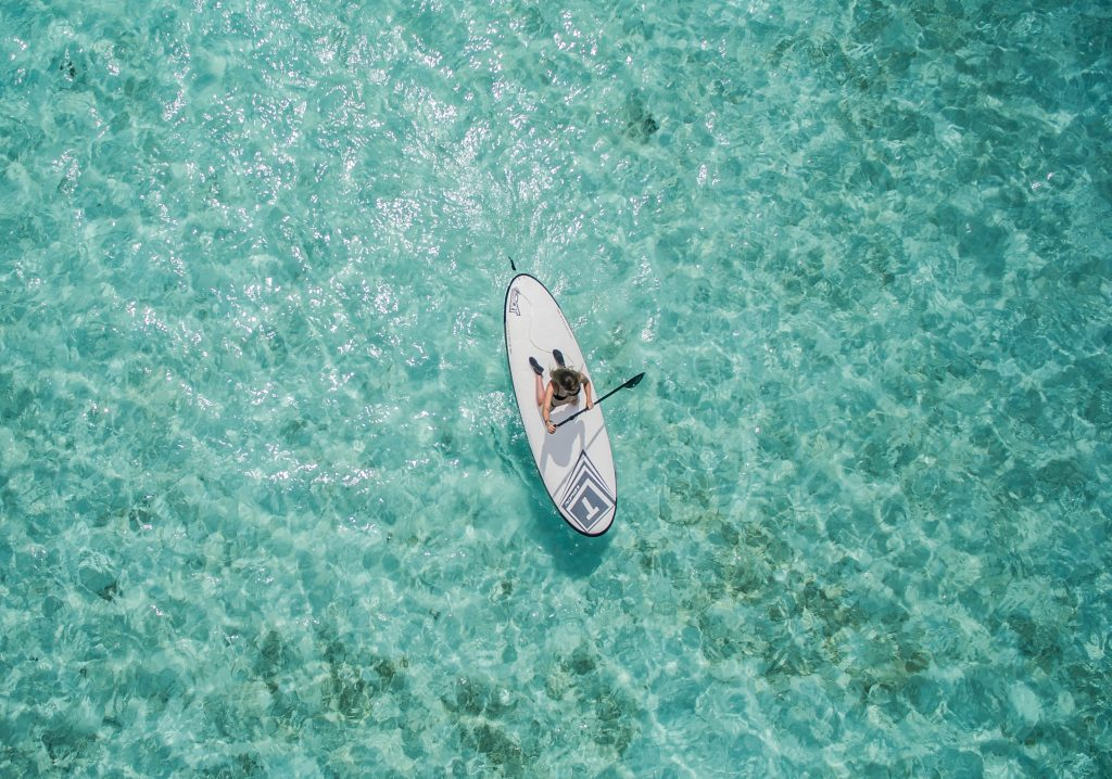 18-Fun-Workouts-to-Get-You-Unstuck-Motivated-in-Life-a-Man-on-a-White-Stand-up-Paddleboard