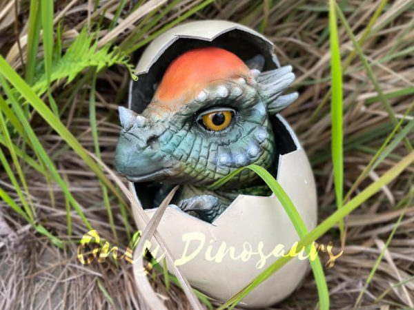 a baby blue-green dinosaur with a red-orange skull inside an egg