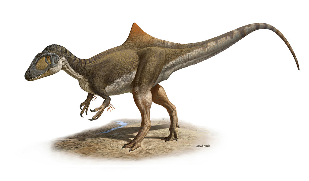 a brown dinosaur with a humped back and feathered arms