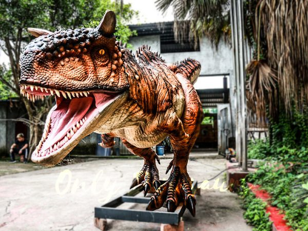 a large red-brown animatronic dinosaur with horns