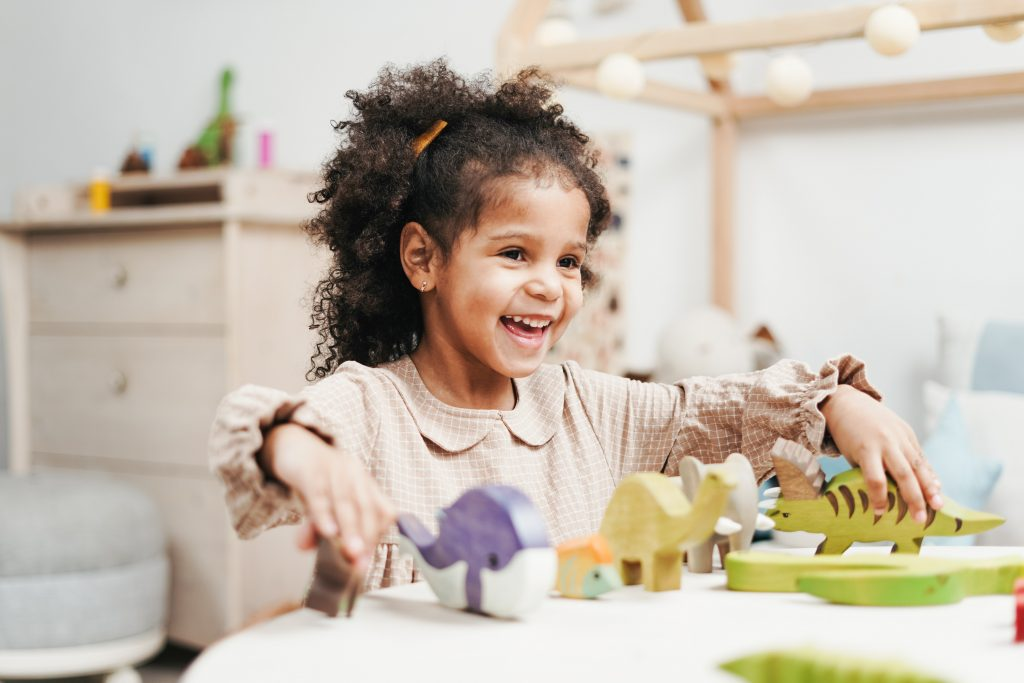 a smiling girl playing with wooden dinosaur toys
