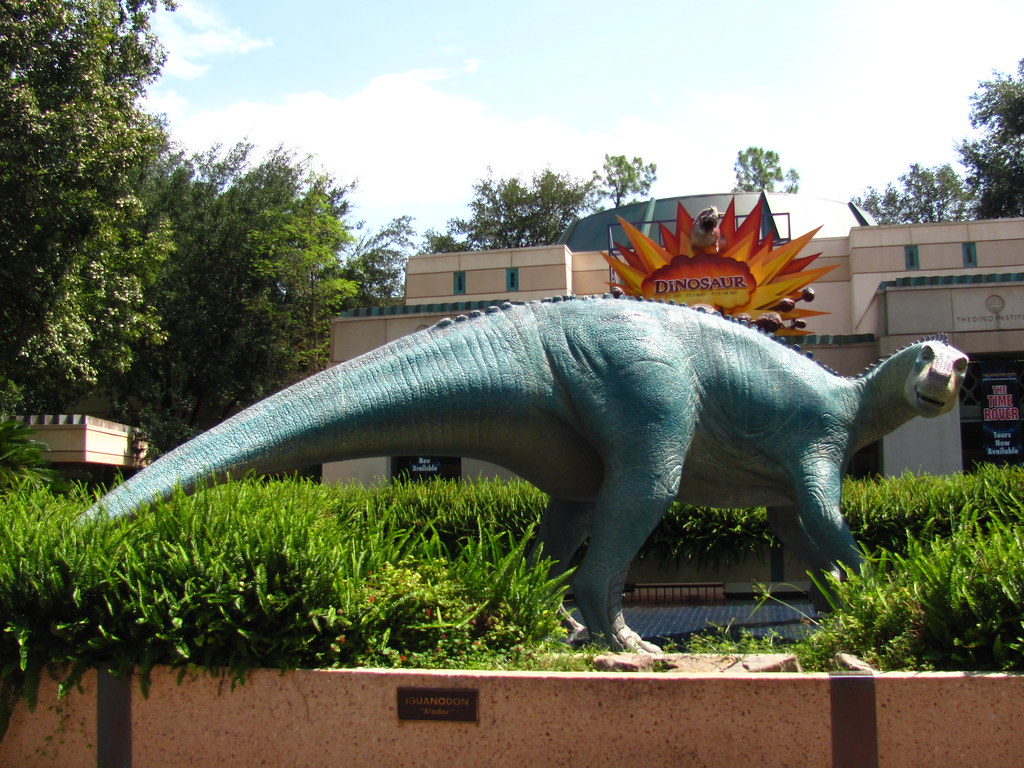long blue-green dinosaur statue in front of a building
