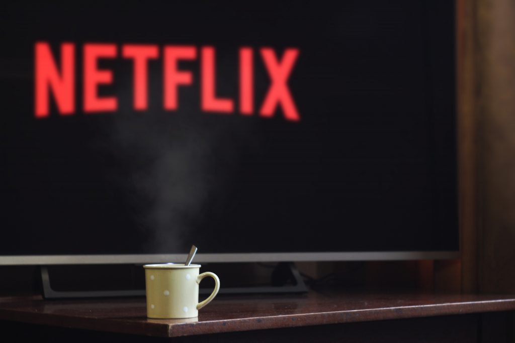 A Coffee Cup in Front of a TV Screen with the Word Netflix Written in Red