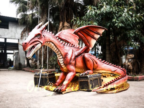 A Red Animatronic Dragon Sitting Beside Brown Treasure Chests