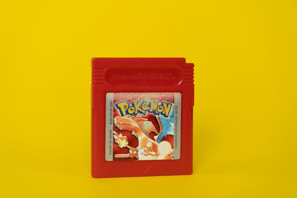 A Red Game Cartridge with a Picture of Charizard in the Middle