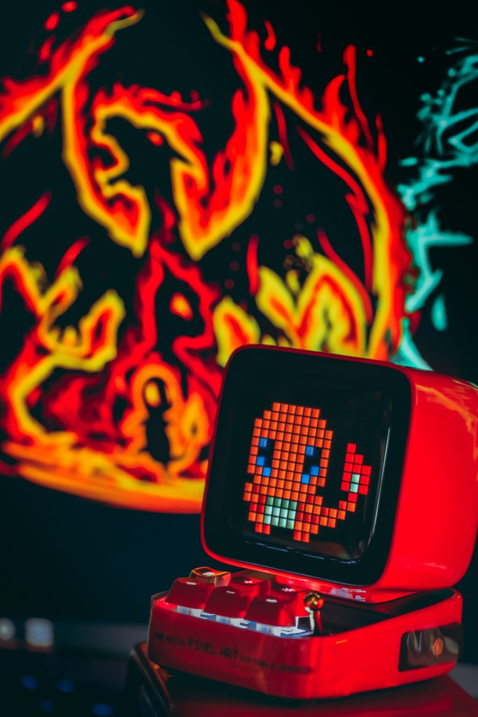 A Red Machine with a Small Orange Dragon on the Screen and a Graphic Art of a Charizard Behind