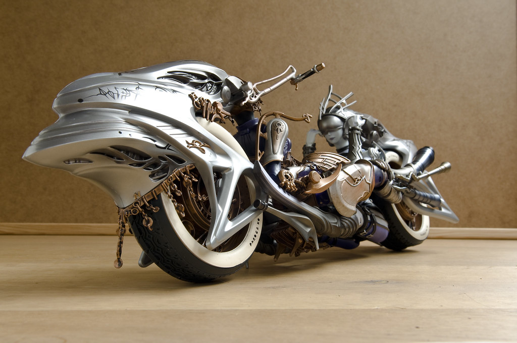 A Silver Motorcycle with a Blue-silver Woman at the End