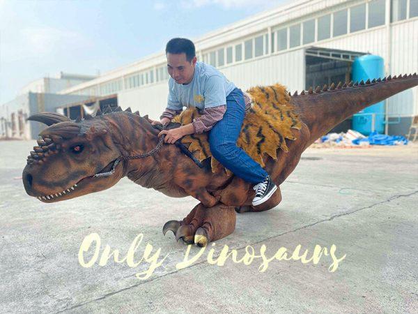 A Man Riding a Squatting Carnotaurus