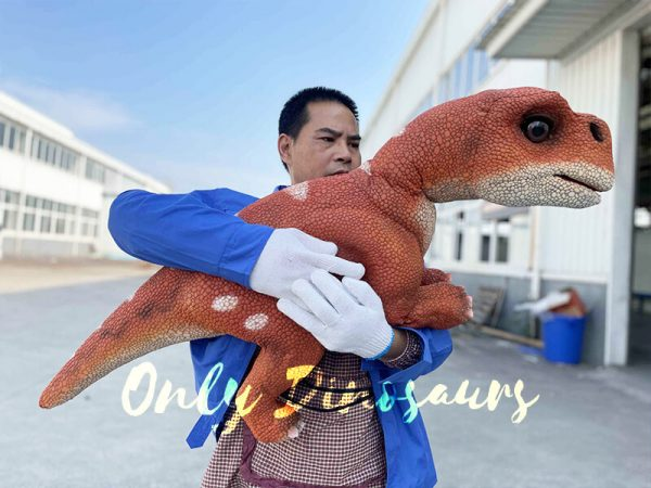 A Man with Blue Clothing Hugging An Orange Baby Dinosaur