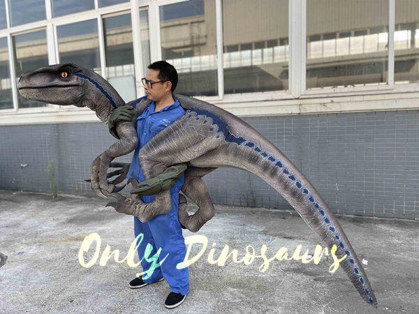 A man with a blue Dinosaur pupet