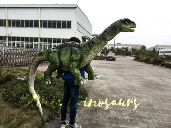 a green long necked dinosaur puppet carried by a man in a blue sweater