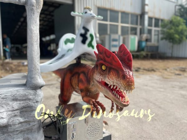an orange dinosaur ride with a fiberglass ladder on the ground