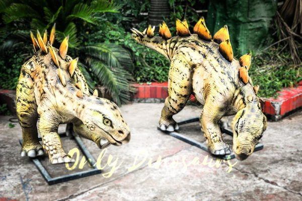 two yellow animatronic dinosaurs with orange plates on their backs