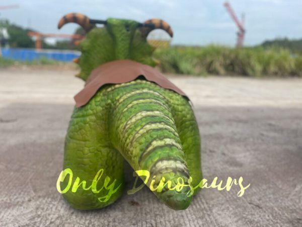 the tail of a green baby dinosaur ride on the ground