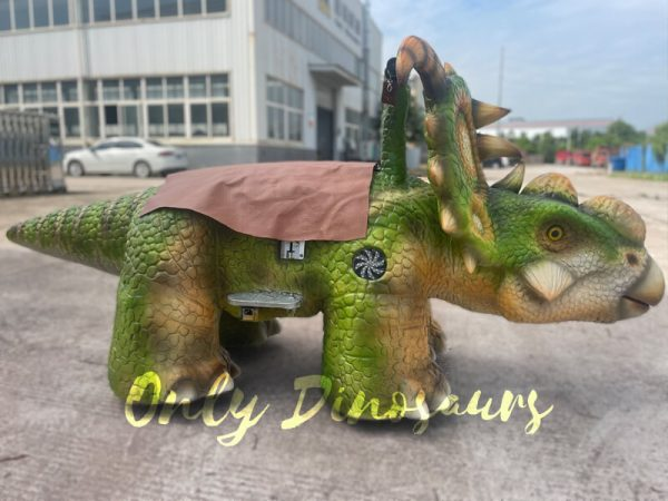 a green baby dinosaur ride on the ground