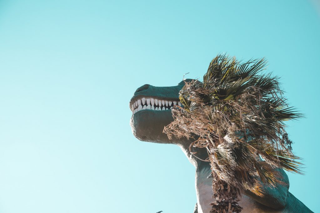 a T. rex statue with a palm tree covering its left eye