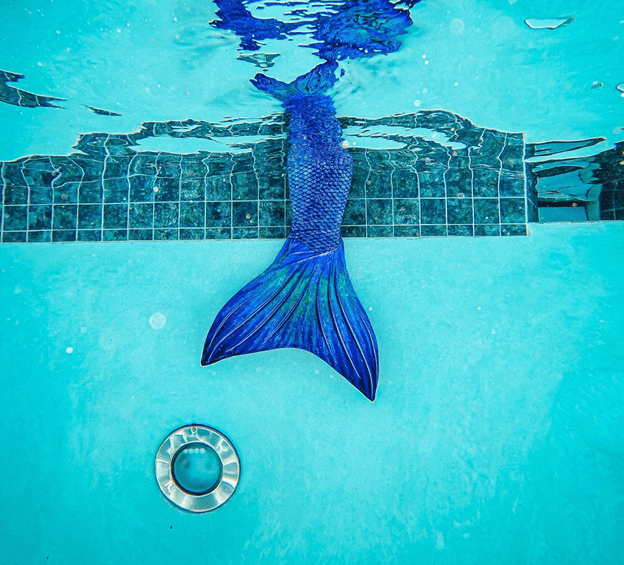 a blue mermaid tail submerges in a pool