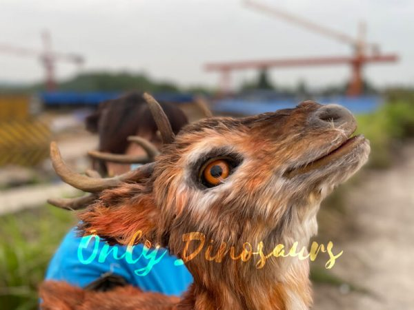 a brown reindeer puppet with a woman in a blue jacket in the background