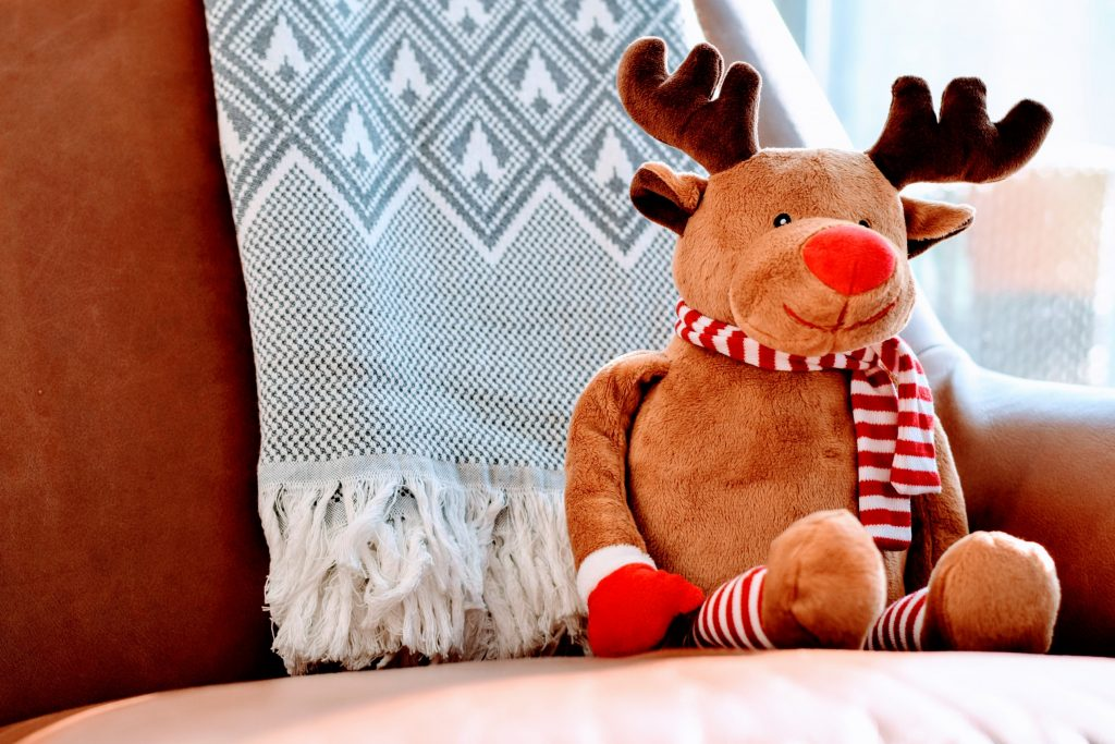 a brown reindeer stuffed toy with a red and white scarf sitting on a brown sofa