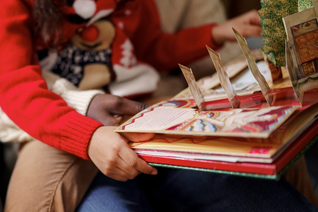 a girl in a red sweater holding a picture book with bright cut-outs