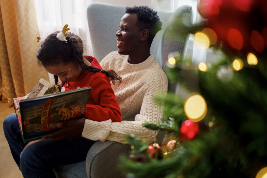 a girl reading a book sitting on a blue-gray couch with her father beside a Christmas tree