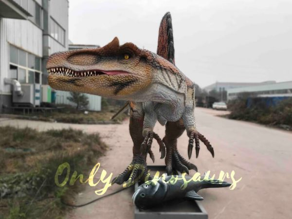 a large brown animatronic dinosaur with a sail-like fin on its back with a fish at its feet