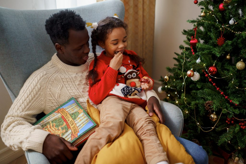 a man in a white sweater holding a Christmas book with his daughter sitting on his lap