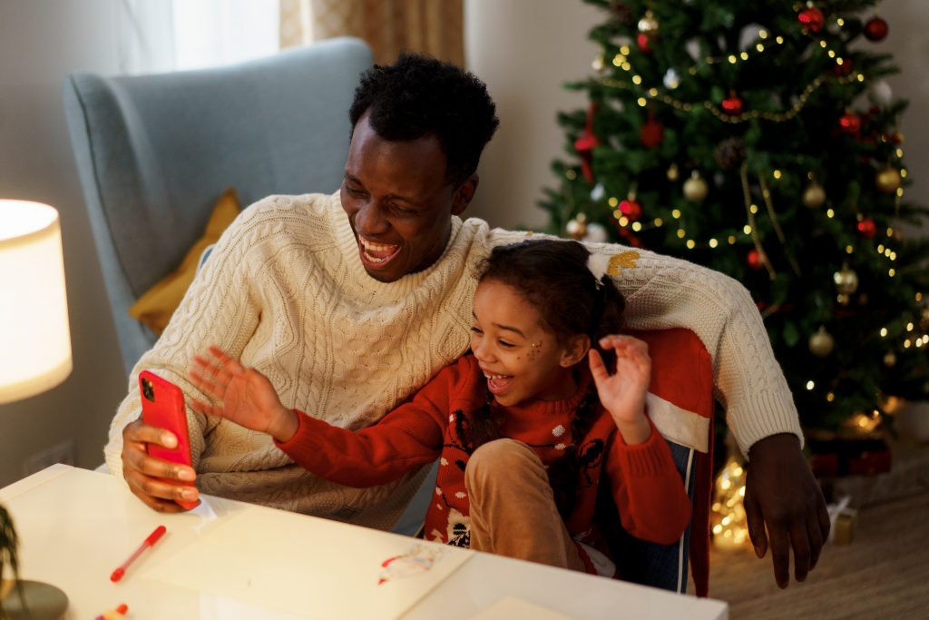 a man in a white sweater laughing with a girl in a red sweater with a Christmas tree in the background