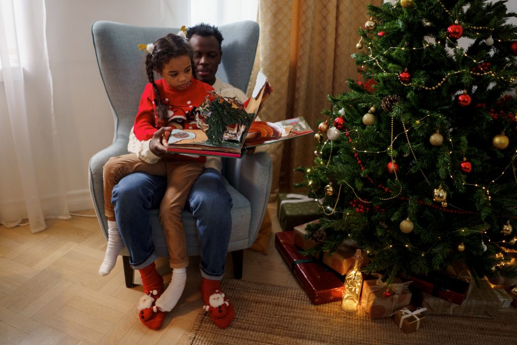 a man sitting on a gray couch with a young girl sitting on his lap reading book beside a christmas tree