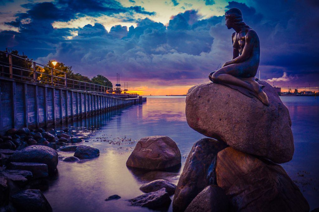 a mermaid statue on top of a pile of rocks beside a body of water