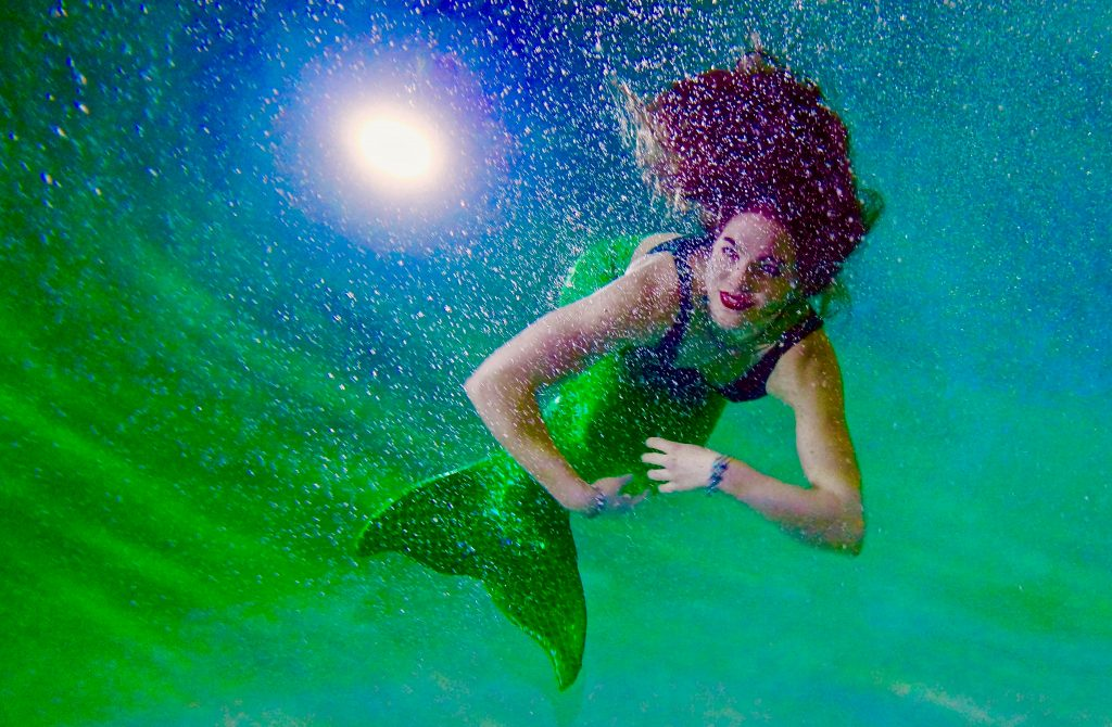 a woman in purple and green mermaid costume swimming underwater in a pool