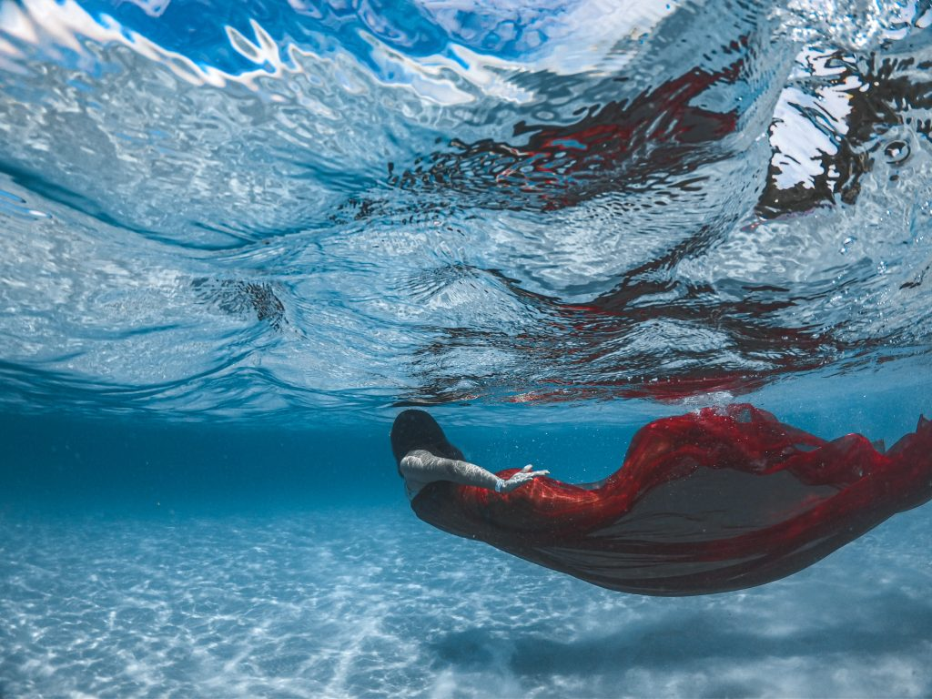a woman wearing a red mermaid costume swimming underwater