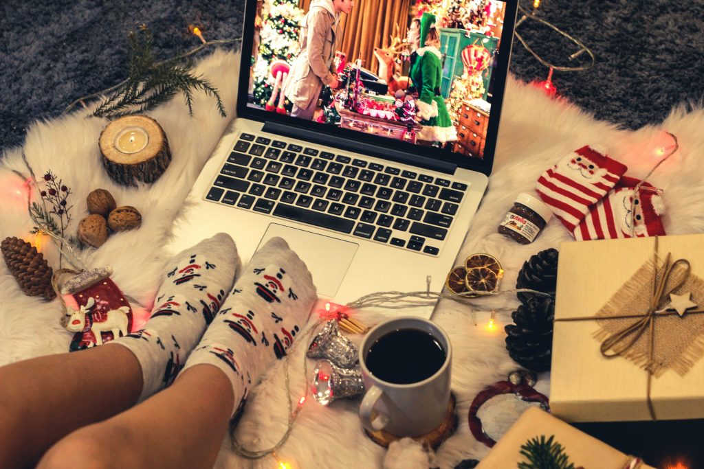 a young child in white socks watching a Christmas movie on a laptop