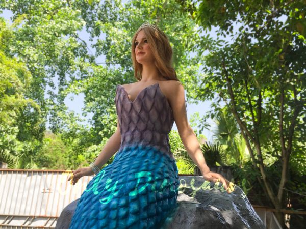 an animatronic mermaid wearing a tiara on her blonde hair, purple-gray scales on her torso, and aquamarine tail