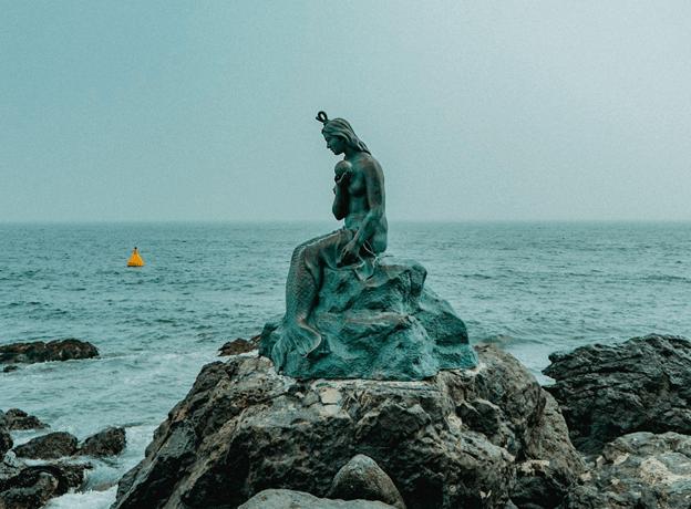 blue-green mermaid statue on a rock beside the sea