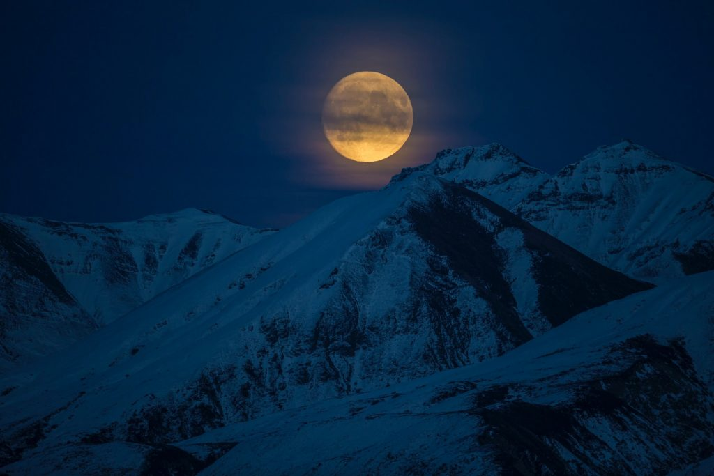 bright moon over snowy mountains at night