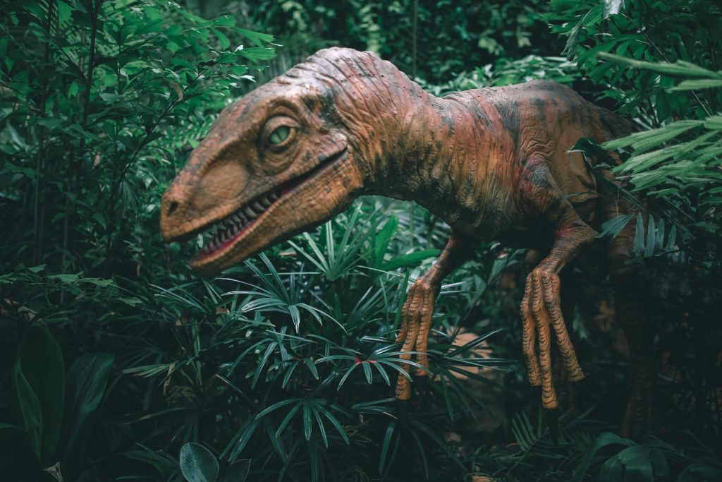 brown open-mouthed dinosaur surrounded by green plants