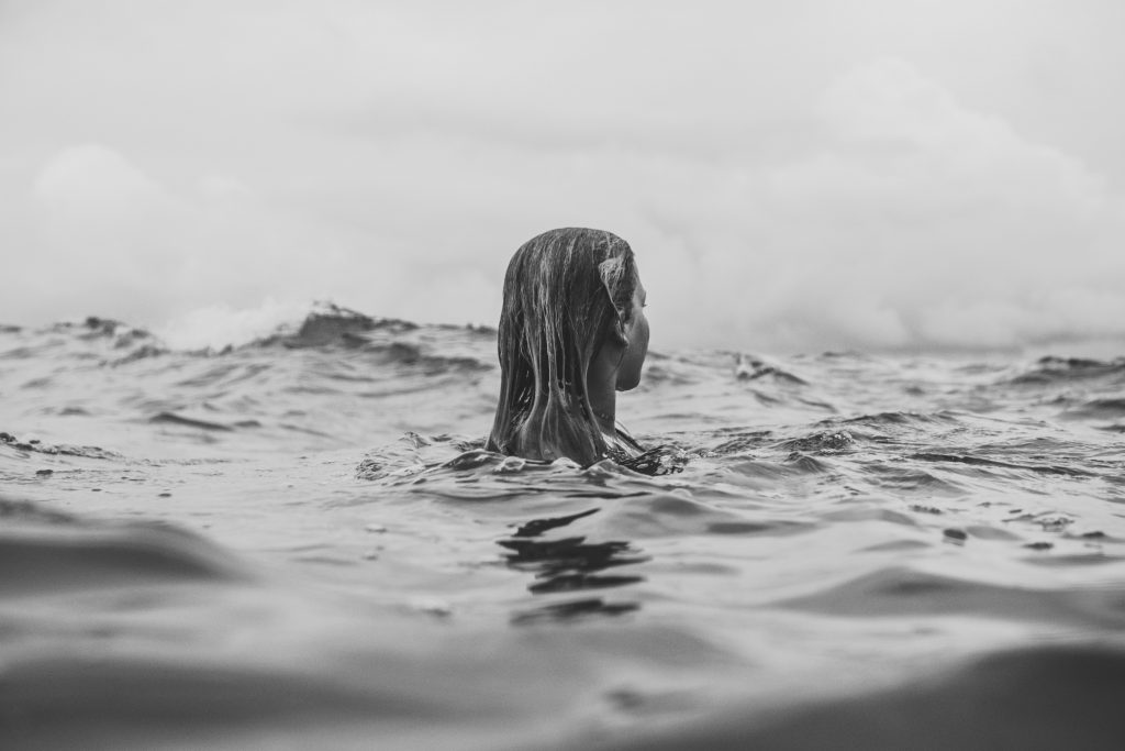 gray-scale photo of a woman in the waters