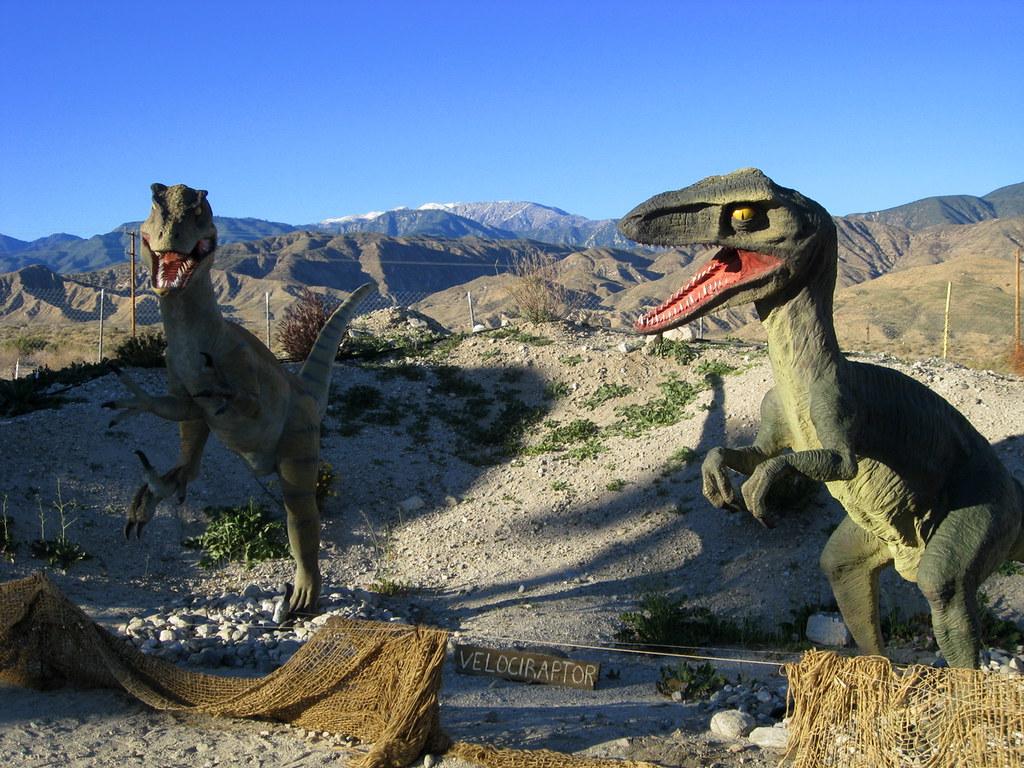green Velociraptor statues in arid land