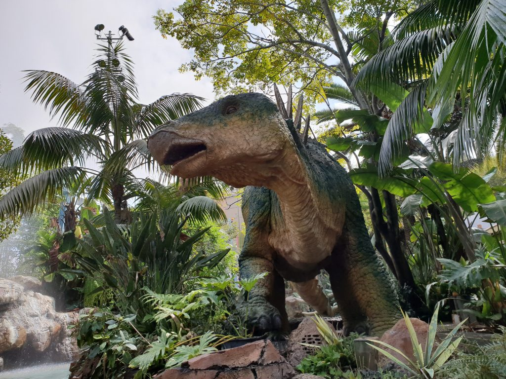 green dinosaur statue in the middle of green plants