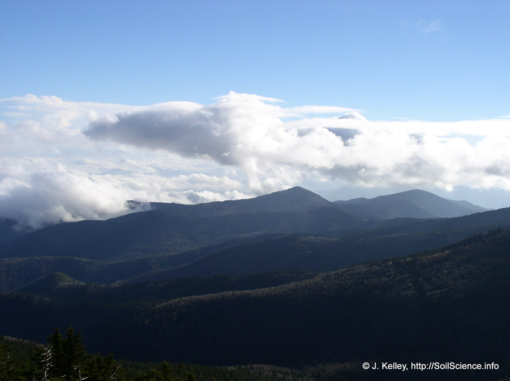green mountain ranges with hovering clouds