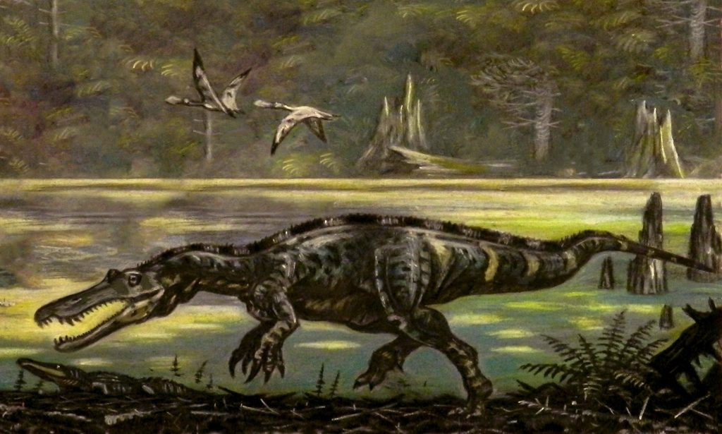 illustration of a crocodile-like dinosaur beside a body of water
