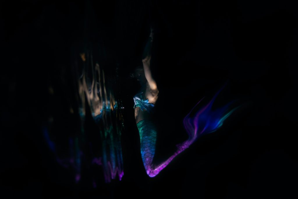 woman in a blue and purple mermaid costume in a black background