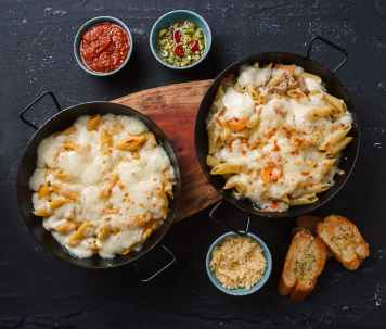 delicious macaroni with cheese served on table with toasted bread and sauce bowls